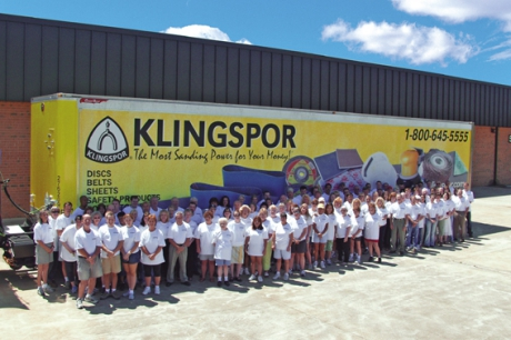 Large group photo of employers and employees outside of KLINGSPOR's plant in Hickory. Everyone is wearing a white shirt and standing in front of a yellow delivery truck.