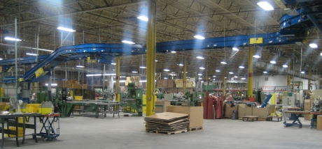 Photograph of inside of Hickory manufacturing plant. Contains green tables, machinery, yellow pedestals, cardboard material. 