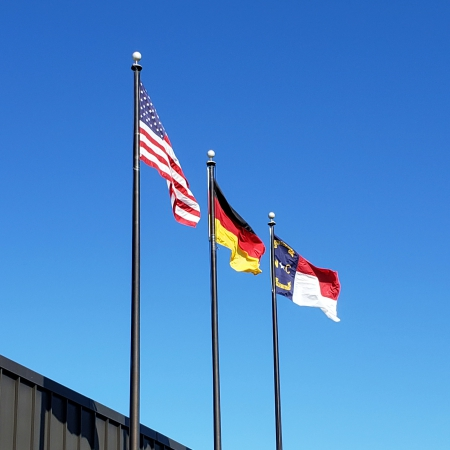 Picture of three flag poles at the Hickory Klingspor Plant. From left to right: United States, Germany, and North Carolina.