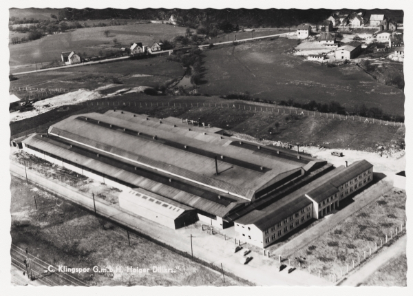 black and white photo of new manufacturing plant. It looks like the size of a sports stadium. It has simple fencing. On the top right, there is a small town in the distance.